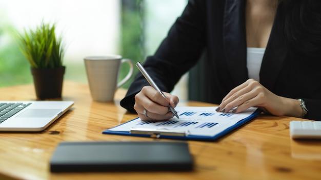 La empresaria en traje negro firma en la propuesta financiera comprobando el informe financiero sosteniendo la pluma