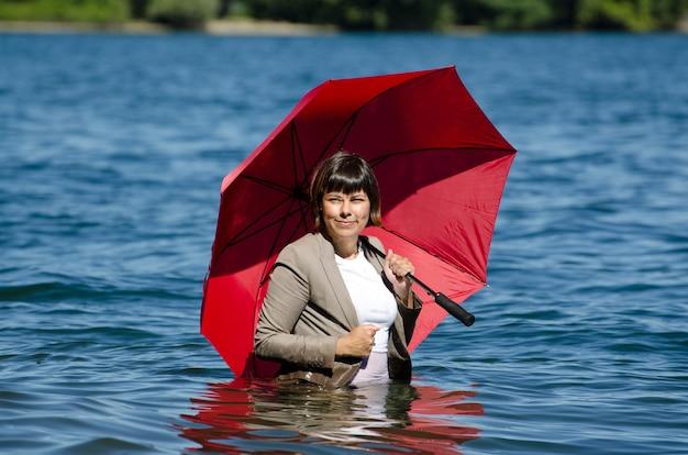 Empresaria en un traje de pie en el agua y sosteniendo una sombrilla roja