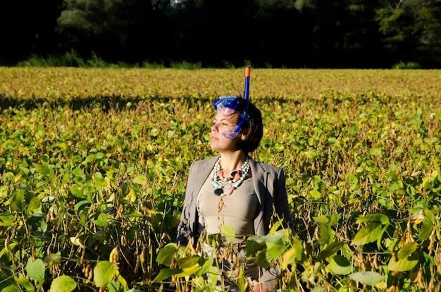 La empresaria en un traje de pie en el campo con una máscara de buceo