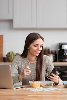 Empresaria tratando de comer y trabajar desde su teléfono