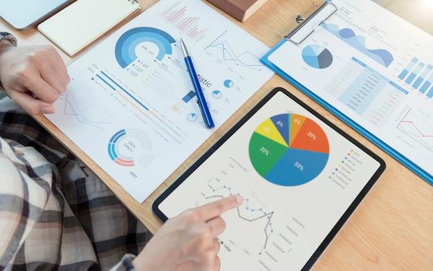 La empresaria usando una tableta para analizar el concepto de éxito de las estadísticas de la estrategia financiera de la empresa y la planificación del futuro en la sala de la oficina.