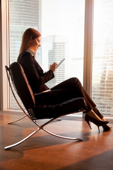 Empresaria usando tableta digital en habitación de hotel