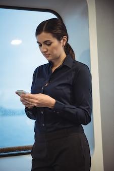Empresaria usando el teléfono mientras está parado en el tren