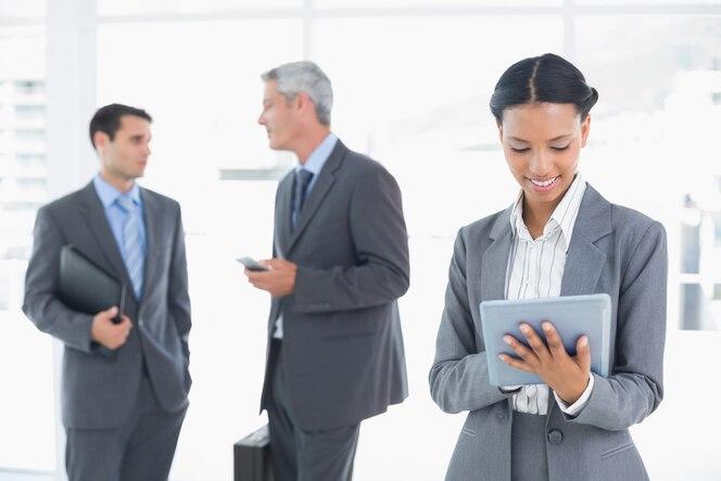 Empresaria usando una tableta con colegas detrás