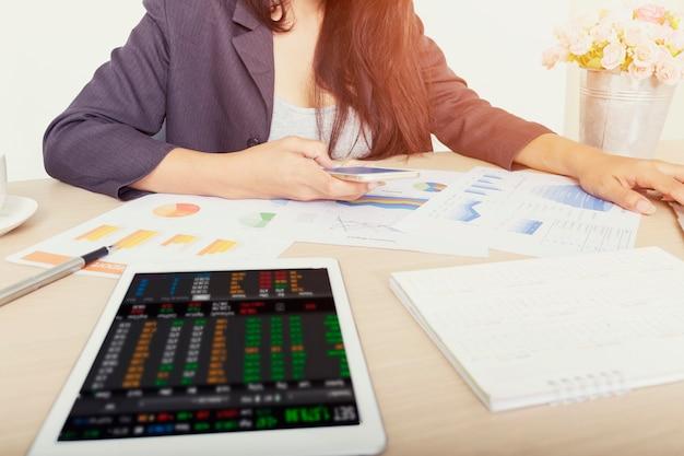 Empresaria utilizando análisis de gráficos de inversión con datos digitales en dispositivos móviles y tabletas