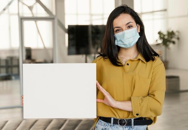 La empresaria vistiendo una máscara médica en el trabajo mientras sostiene una tarjeta en blanco