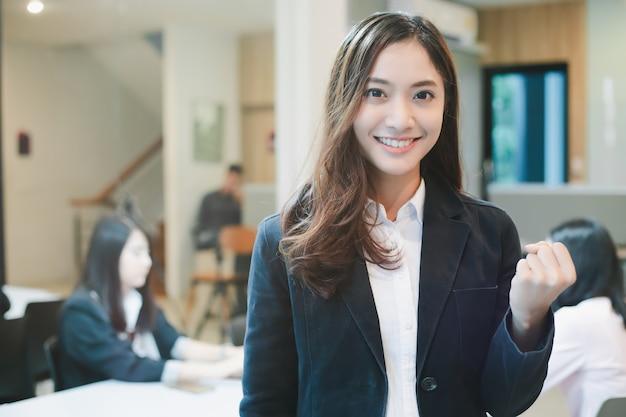 Empresarias asiáticas éxito y concepto ganador: equipo feliz con las manos levantadas celebrando el avance y los logros