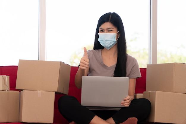 Las empresarias asiáticas jóvenes felices en una máscara muestran los pulgares hacia arriba de alegría con el éxito en los negocios