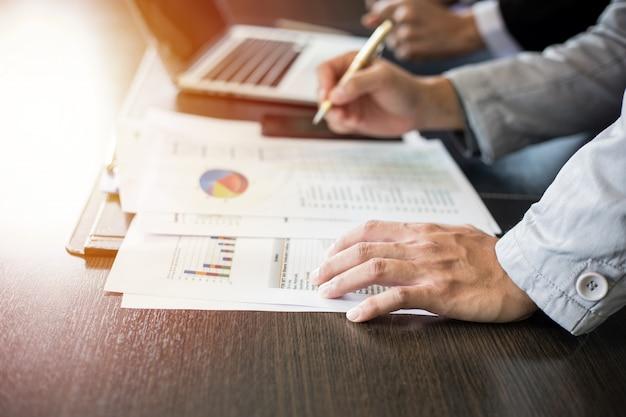 Empresarias asiáticas con una pluma y documentos de análisis en la mesa de oficina con computadora portátil y diagrama financiero gráfico trabajando
