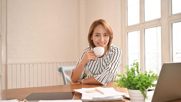 Empresarias asiáticas que sostienen un café en lugar de trabajo de la oficina.