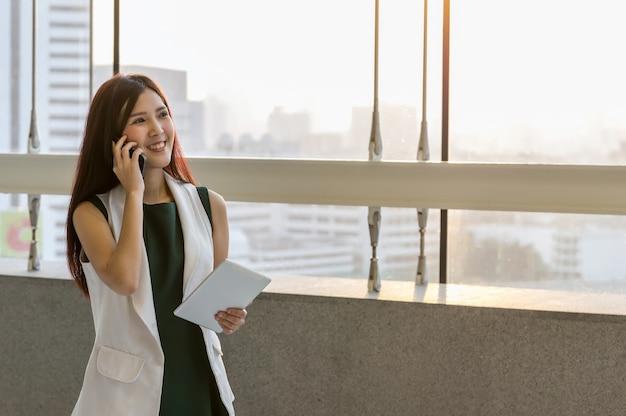 Empresarias asiáticas sosteniendo la tableta y llamando al teléfono con la conferencia