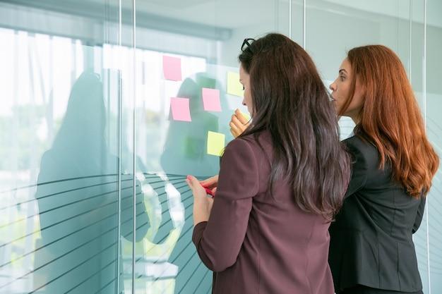Empresarias concentradas pegando notas en la pared de vidrio en la sala de conferencias