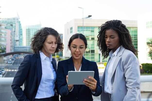 Empresarias concentradas con tableta digital