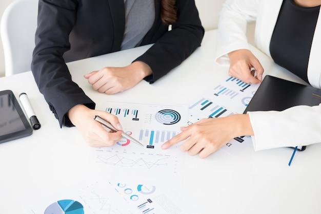Empresarias discutiendo documentos gráficos financieros