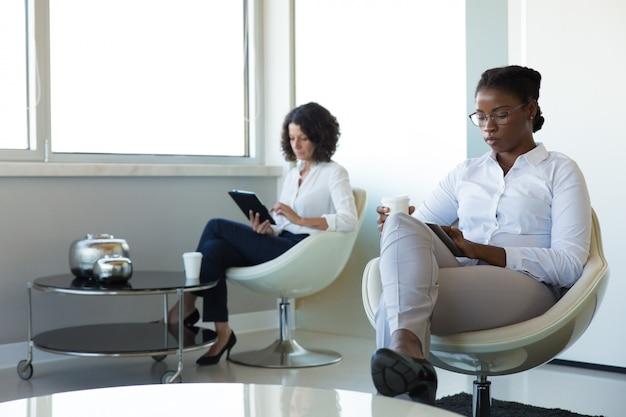 Empresarias disfrutando de vacaciones en el salón de la oficina