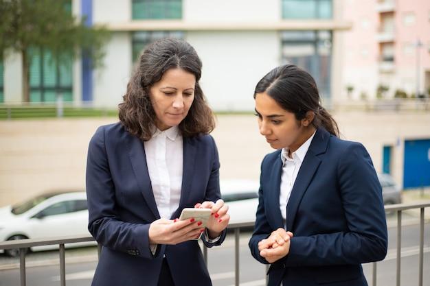 Empresarias enfocadas que usan teléfonos inteligentes