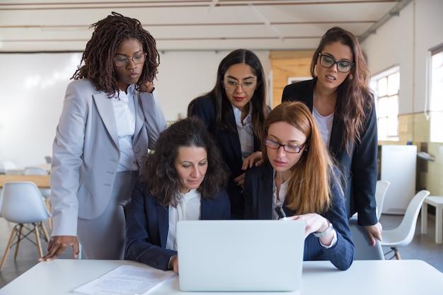 Empresarias enfocadas usando laptop en la oficina