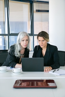 Empresarias entusiasmadas centradas mirando la pantalla del portátil mientras están sentados a la mesa con tazas de café en la oficina. vista frontal. concepto de comunicación y trabajo en equipo