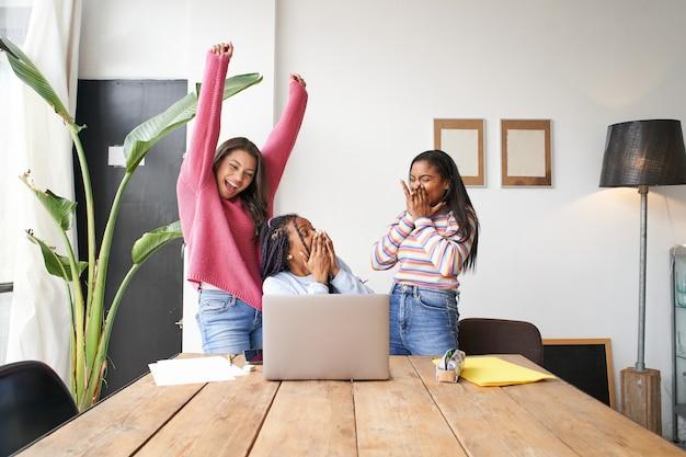 Empresarias entusiasmadas levantando la mano celebrando increíbles resultados en línea socios felices motivados