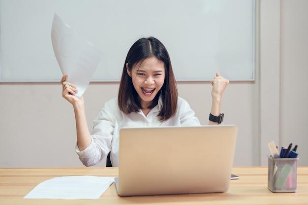 Las empresarias están felices de tener éxito en el trabajo y muestran el documento en la mesa en la parte posterior de la oficina