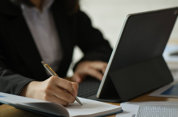 Las empresarias están usando una computadora portátil y tomando notas del trabajo en el escritorio de la oficina.