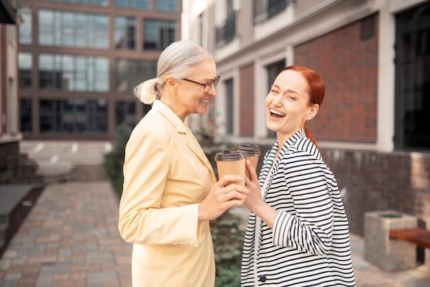 Empresarias felices. cintura para arriba de dos señoras de negocios contentas en ropa de moda riendo mientras está al aire libre en frente de un edificio de oficinas