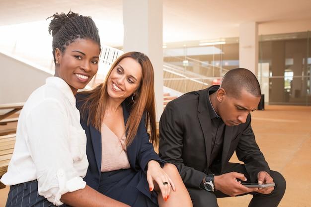 Empresarias felices que sonríen en la cámara y el hombre que usa el teléfono móvil