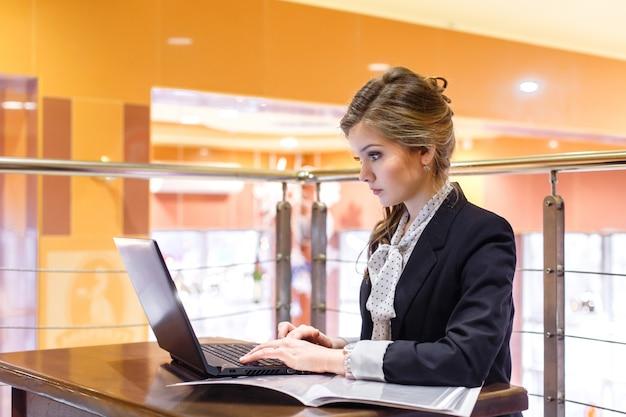 Empresarias hermosas jovenes que se sientan en un café y que trabajan en una computadora portátil