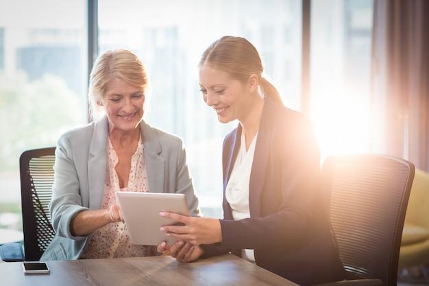 Empresarias interactuando con tableta digital