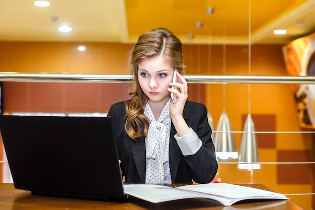 Empresarias jovenes que se sientan en un café con un ordenador portátil y que hablan en el teléfono móvil