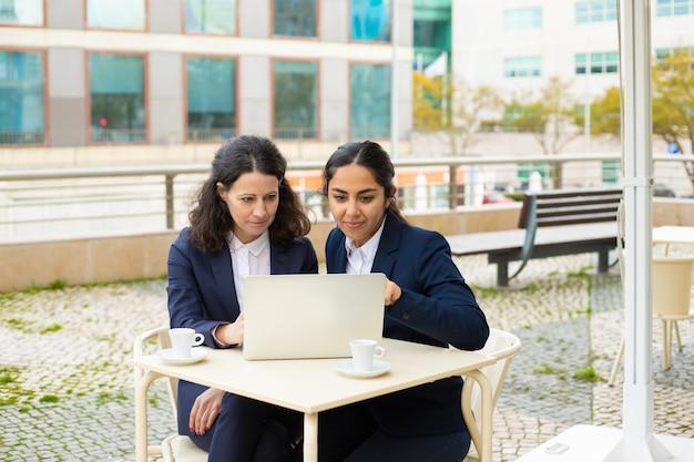 Empresarias con laptop en café al aire libre
