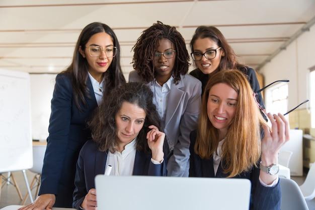 Empresarias multiétnicas usando laptop en la oficina