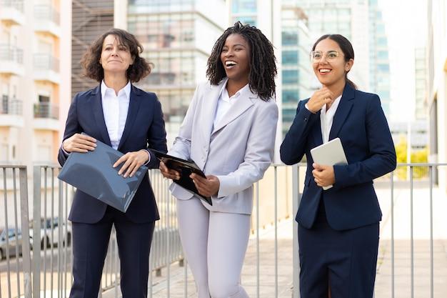 Empresarias con papeles y dispositivo digital. colegas femeninas multiétnicas que sostienen la pc y los papeles de la tableta al aire libre. concepto de negocio