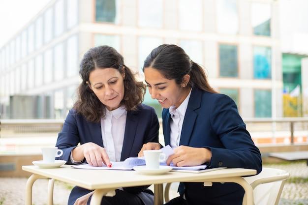 Empresarias que trabajan con documentos en café al aire libre