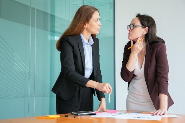 Empresarias serias discutiendo documentos estadísticos y de pie cerca del escritorio en la sala de conferencias