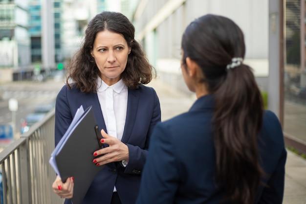 Empresarias serias discutiendo el trabajo