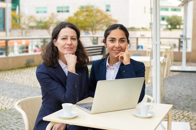 Empresarias sonriendo en café al aire libre