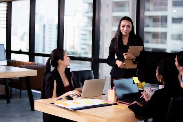 Empresarias sonriendo y discutiendo con un colega en reunión