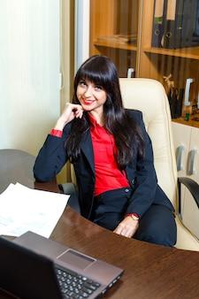 Empresarias sonrientes que se sientan en la tabla en la oficina con papeleo y el ordenador portátil