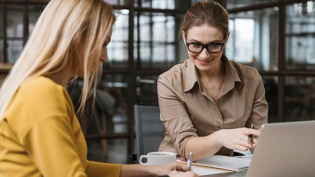 Empresarias sonrientes que trabajan con el portátil en el escritorio en el interior
