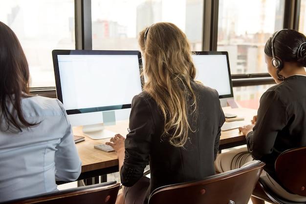 Empresarias de telemarketing con auriculares trabajando en computadoras