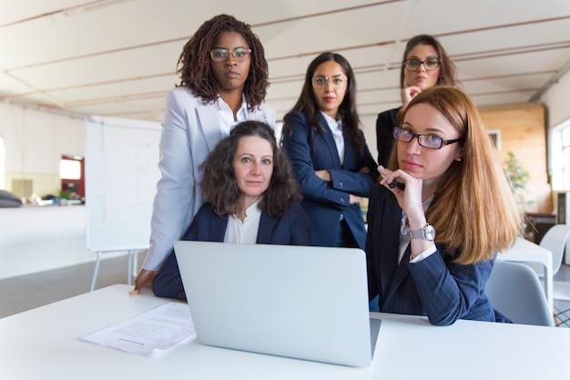 Empresarias usando laptop y mirando a cámara
