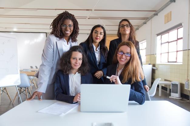 Empresarias usando laptop y sonriendo a la cámara