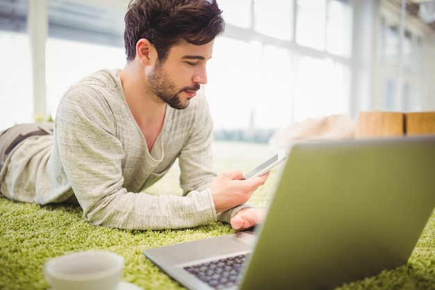 Empresario acostado en la alfombra mientras usa la computadora portátil y el teléfono móvil