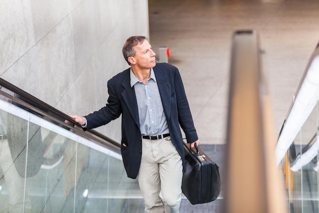 Empresario adulto con maleta en la escalera mecánica de la ciudad.
