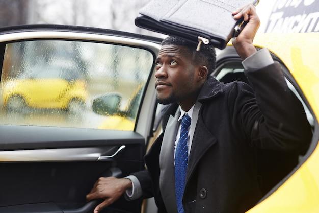 Empresario africano dejando taxi bajo la lluvia