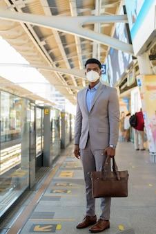 Empresario africano en la plataforma de la estación de tren con mascarilla mientras espera el tren
