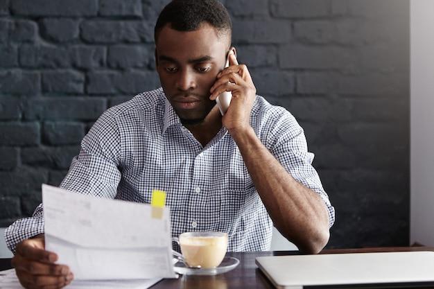 Empresario africano serio sosteniendo un pedazo de papel en una mano y un teléfono móvil en la otra