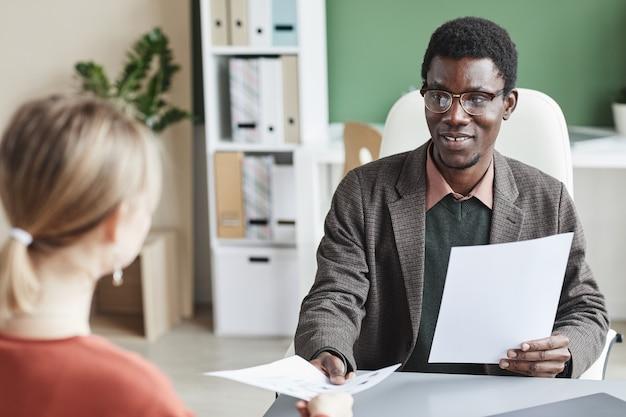Empresario africano tomando un currículum del empleado durante la entrevista de negocios en la oficina