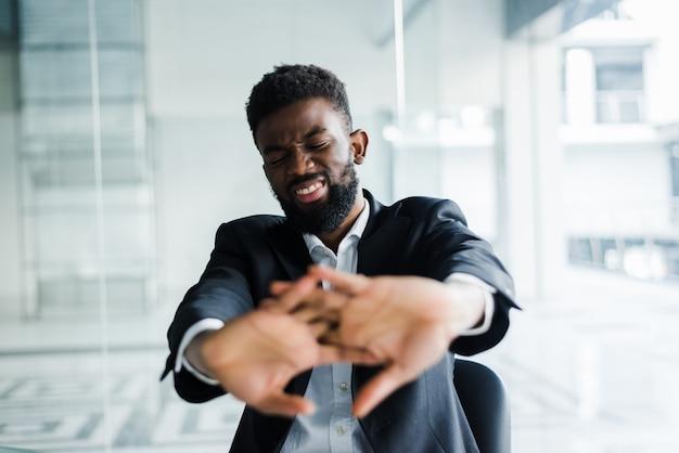 Empresario africano tomar un descanso durante la jornada laboral estirando las manos dedos comenzando el trabajo de oficina